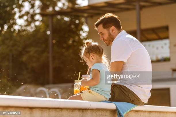 father and daughter drinking fresh juice by the pool - june stock pictures, royalty-free photos & images
