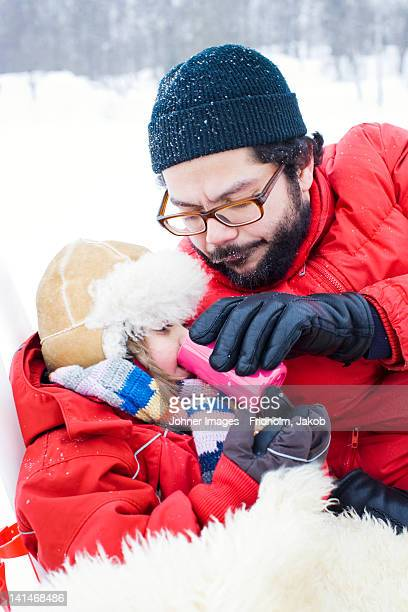 Father and daughter drinking from flask in winter landscape