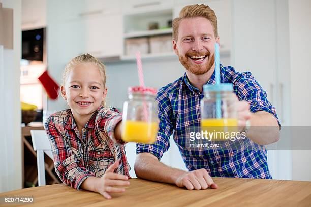 Father and daughter drinking orange juice