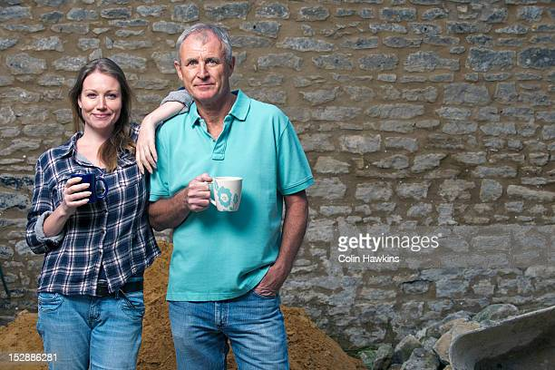 Father and daughter drinking tea in yard