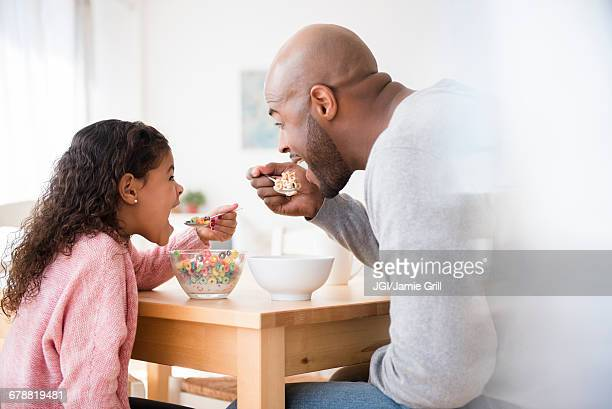 Father and daughter eating cereal at table