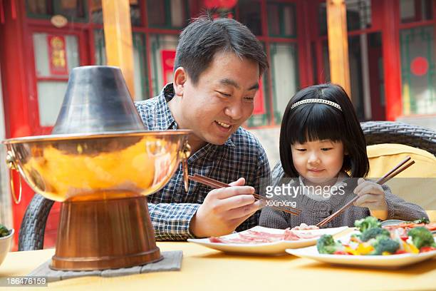 Father and daughter eating Chinese food outside