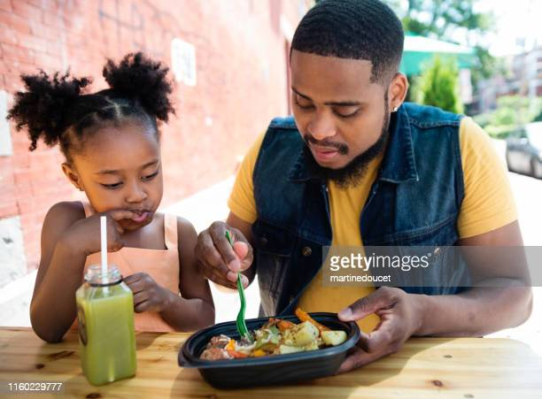 Father and daughter eating take out food outdoors.