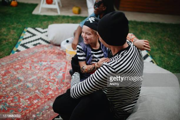 father and daughter embracing during backyard movie night - scaredastronaut stock pictures, royalty-free photos & images