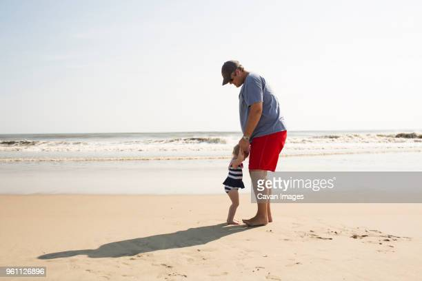 father and daughter enjoying at beach against sky during sunny day - outer banks stock pictures, royalty-free photos & images