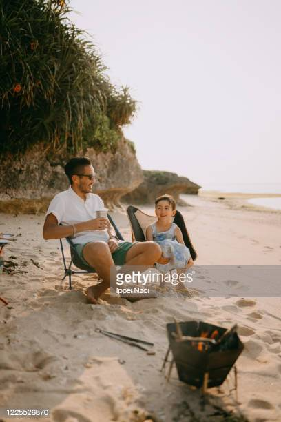 father and daughter enjoying beach campsite at sunset, okinawa, japan - ippei naoi stock pictures, royalty-free photos & images