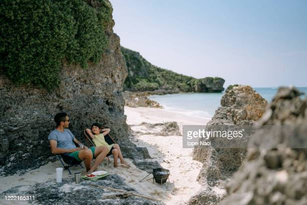 father and daughter enjoying beach campsite, okinawa, japan - ippei naoi stock pictures, royalty-free photos & images