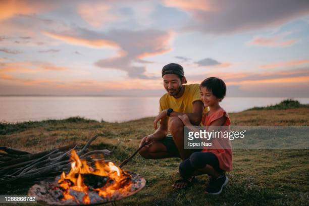 father and daughter enjoying campfire at campsite at sunset - love stock pictures, royalty-free photos & images
