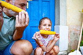 father daughter enjoying eating corn outdoors