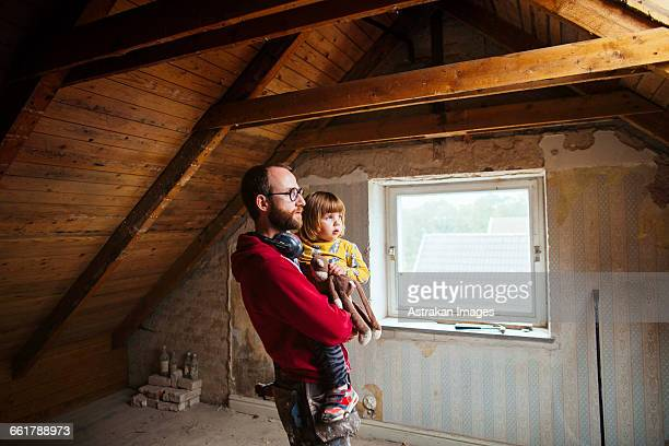 Father and daughter examining attic under construction