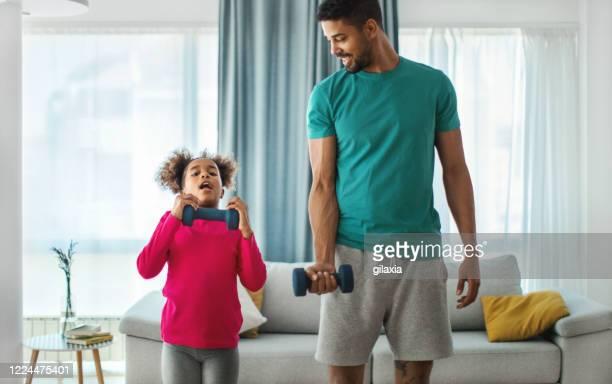 自宅で運動する父と娘。 - kids weightlifting ストックフォトと画像