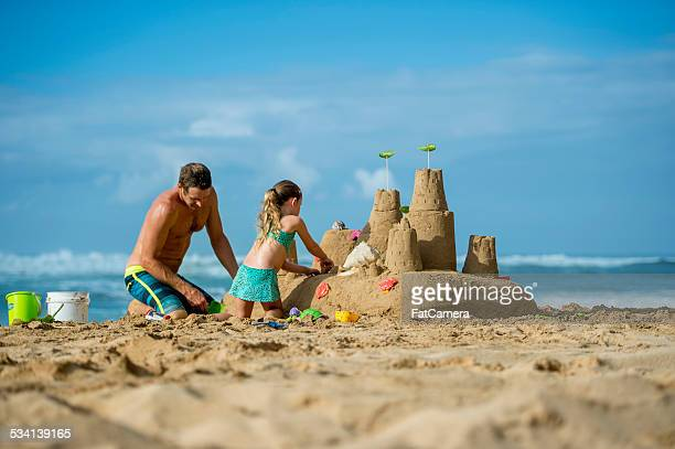 Father and daughter family building sand castle on beach