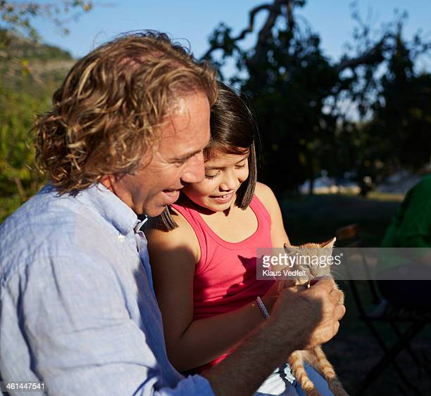 father and daughter feeding little red kitten - klaus vedfelt mallorca stock pictures, royalty-free photos & images