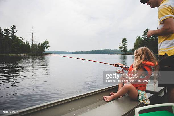 Father and daughter fishing from boat on river