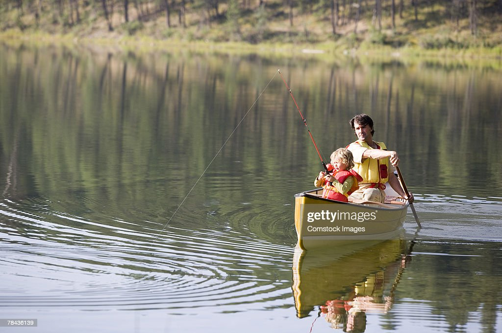 Father and daughter fishing from canoe : Stockfoto