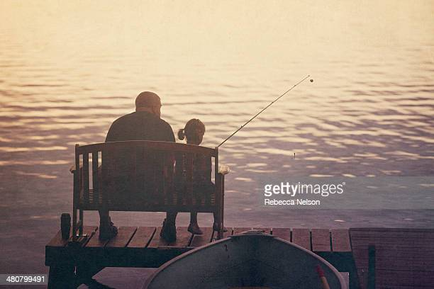 Father and daughter fishing off of pier