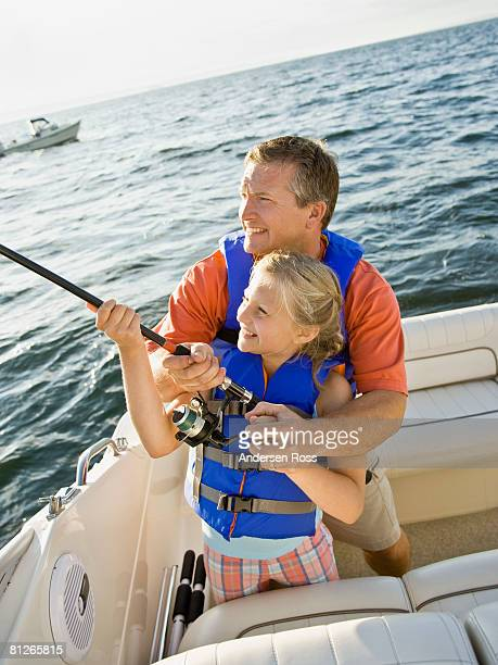 Father and daughter fishing on boat