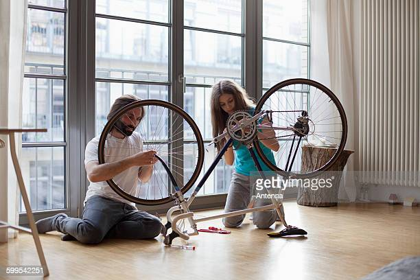 Father and daughter fixing bicycle together at home