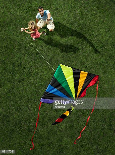 A father and daughter flying a kite together