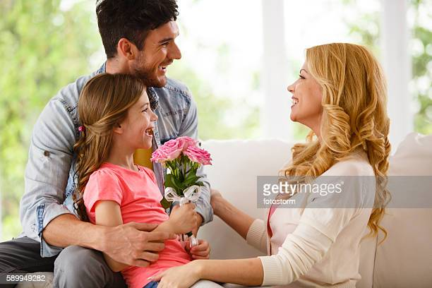 Father and daughter giving flower to mother