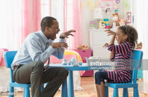 father and daughter growling at tea party in playroom - tea party stock pictures, royalty-free photos & images