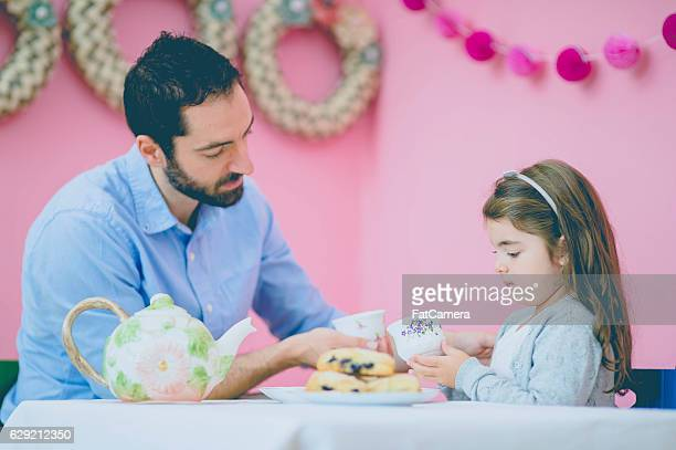 Father and daughter having a conversation during their tea party