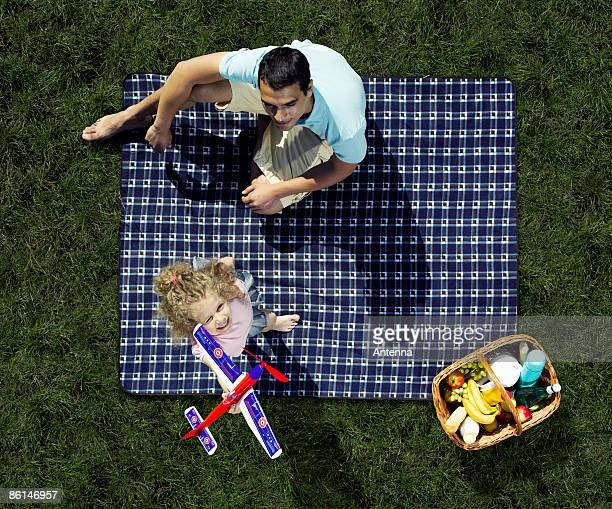 A father and daughter having a picnic and playing with a toy airplane