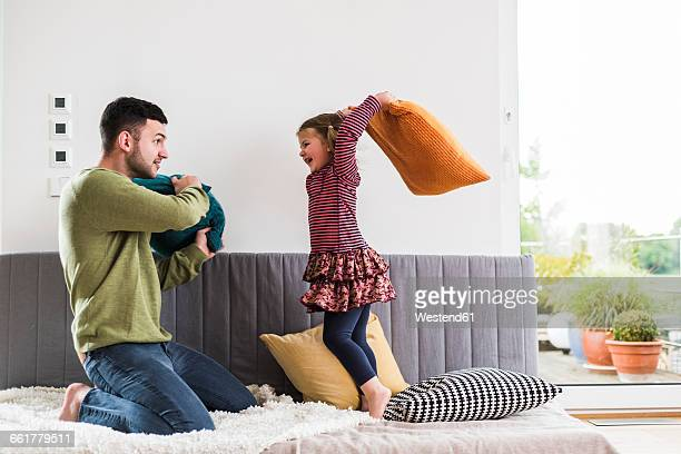 Father and daughter having a pillow fight