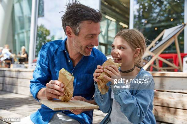 Father and daughter having a snack at an outdoor cafe