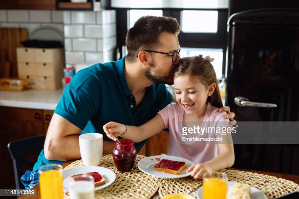 Father and daughter having breakfast at home