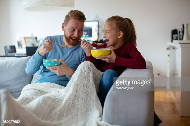 father and daughter having breakfast in living room - genderblend stock pictures, royalty-free photos & images
