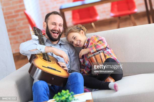 father and daughter having fun at home - percussion instrument stock pictures, royalty-free photos & images