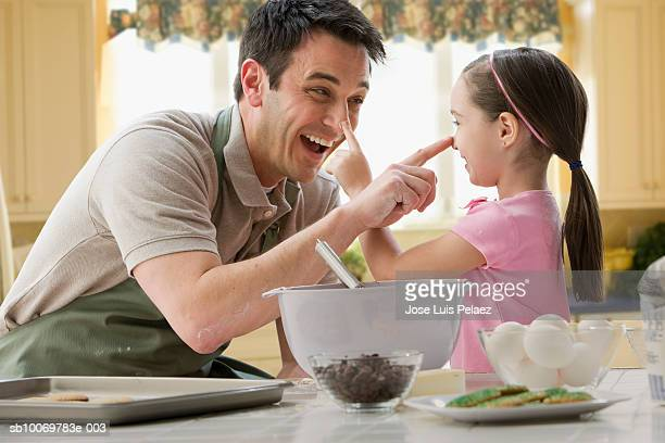 Father and daughter (4-5) having fun baking