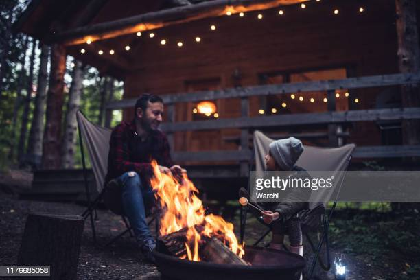 father and daughter  having fun by the campfire - cottage exterior stock pictures, royalty-free photos & images