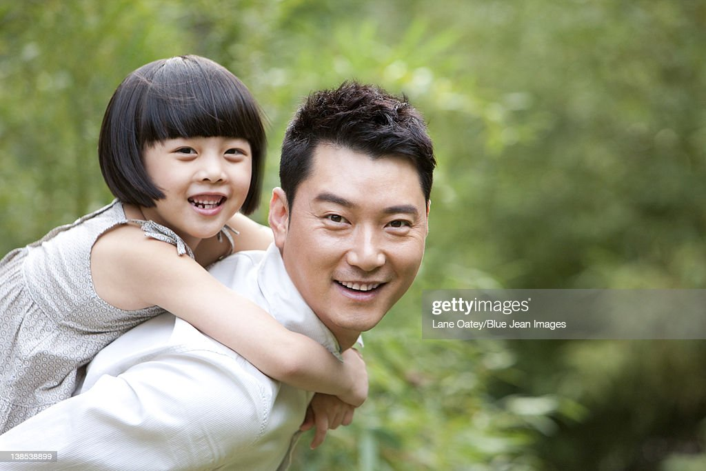 Father and daughter having fun in garden : Stock Photo