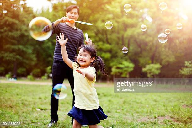 father and daughter having fun in park with soap bubbles - asian and indian ethnicities stock pictures, royalty-free photos & images