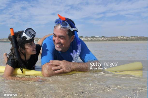 father and daughter having fun on the beach - rafael ben ari stock-fotos und bilder