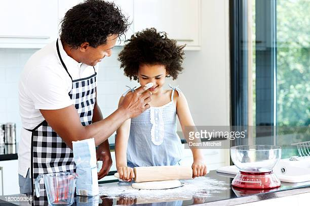 Father and daughter having fun while cooking