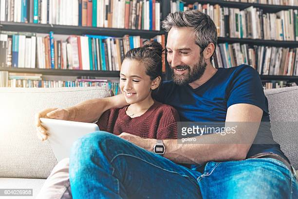 father and daughter having fun with digital tablet - fille de 12 ans photos et images de collection