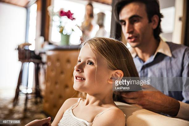 Father and daughter having hair done before a celebration event