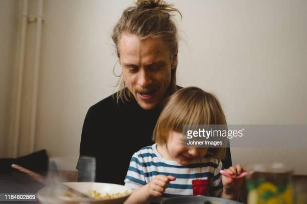 father and daughter having meal - hommes d'âge moyen photos et images de collection