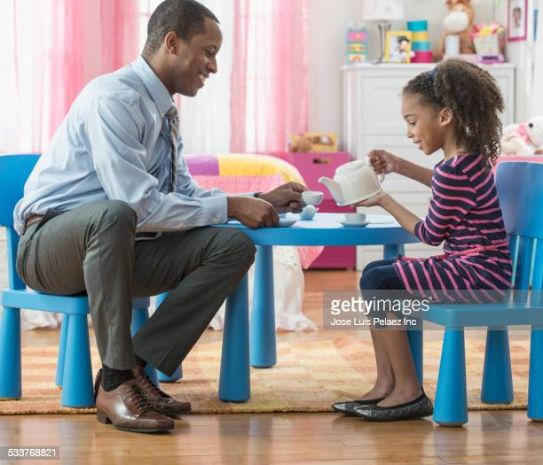 father and daughter having tea party in playroom - tea party stock pictures, royalty-free photos & images