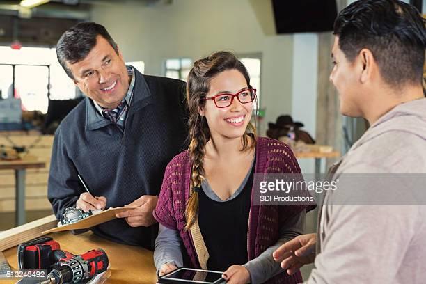 Vater und Tochter hilft Kunden in kleinen Tischlerarbeit Geschäft