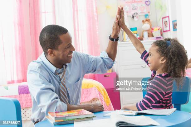 Father and daughter high-fiving during homework in playroom