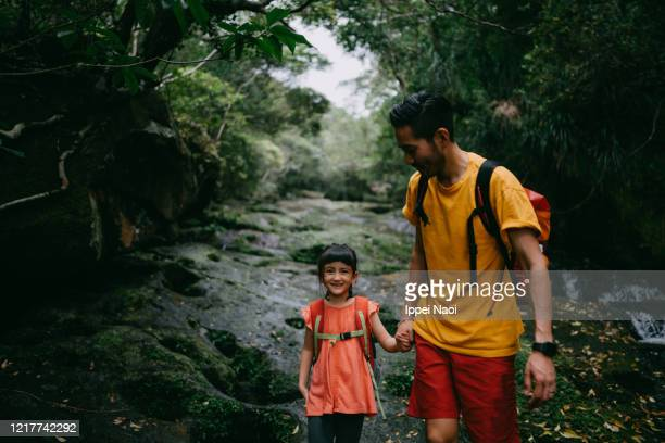 father and daughter hiking through river in jungle, okinawa, japan - reality fernsehen stock pictures, royalty-free photos & images