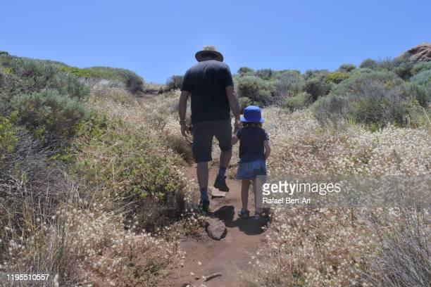 father and daughter hiking together - rafael ben ari stock-fotos und bilder