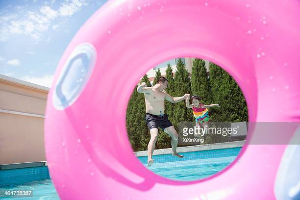 father and daughter holding hands and jumping into the pool, seen through an inflatable pink tube  - pink tube photos et images de collection