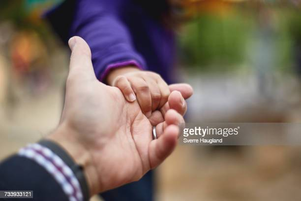 Father and daughter holding hands, close-up