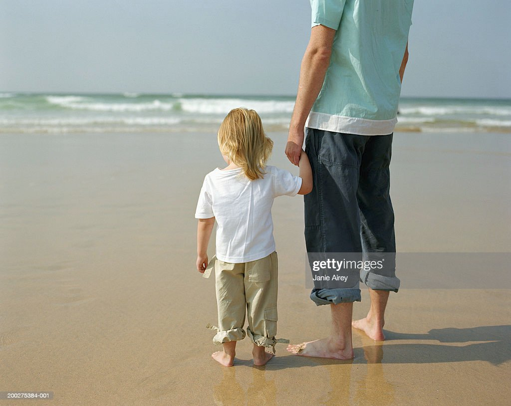 Father And Daughter Holding Hands On Beach Rear View Stockfoto