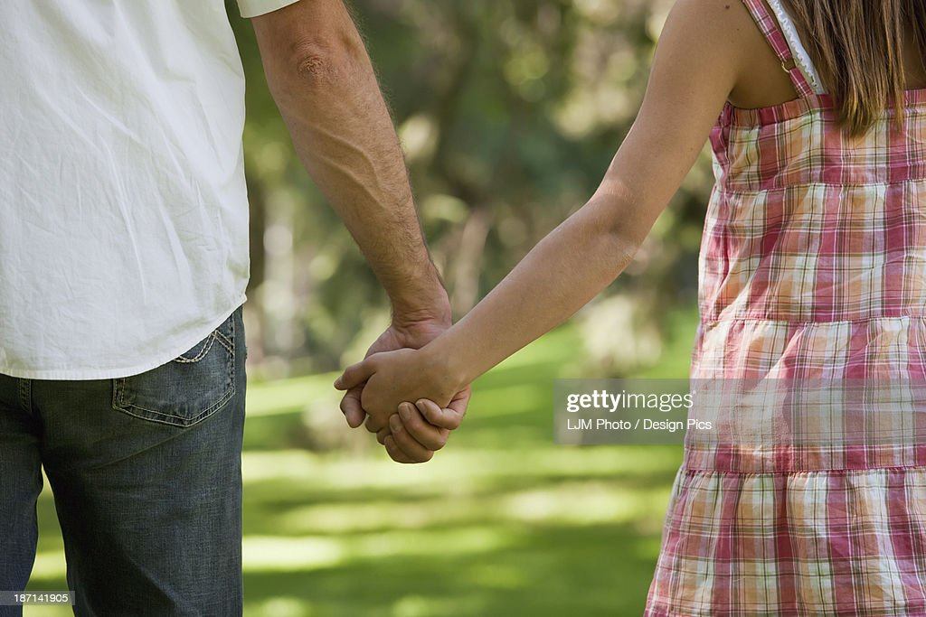 Father And Daughter Holding Hands Walking In The Park Stock Photo